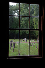Church window looking out at the graveyard