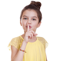 Little girl has put forefinger to lips as sign of silence