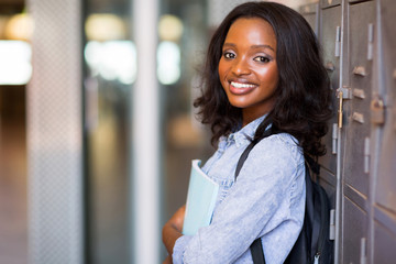 female african student standing next to locker