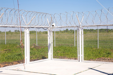 Camcorder and barbed wire on angle fence