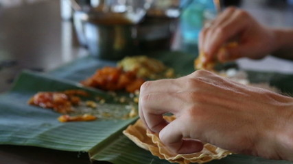 man eats rice  with flat cake from leaf  and focus is changes