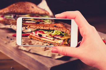 Using smartphones to take photos of club sandwich with instagram
