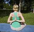 blonde real girl doing yoga in green park