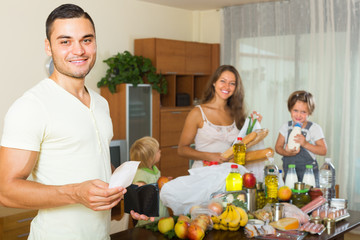 Family of four with bags of food