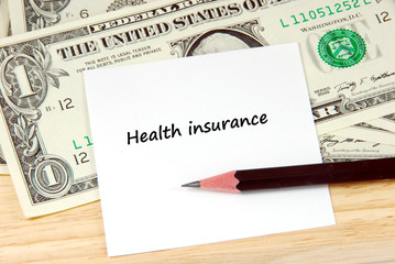 Health insurance words on note pad and money, financial concept