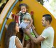 Children with parents at playground ladder