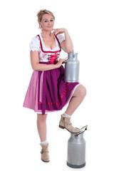 Frau im Dirndl mit Milch Kannen posiert im weißen Raum
