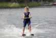 Blonde Boy learning to waterski on a lake - 77976713