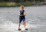 Blonde Boy learning to waterski on a lake
