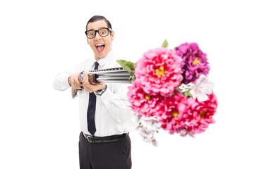 Joyful man shooting flowers from a shotgun