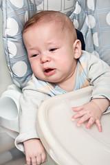 kid cries sitting in a chair for feeding