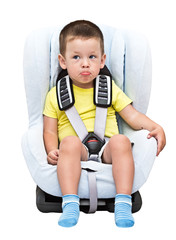 three-year-old boy sits in an auto children's chair, isolated
