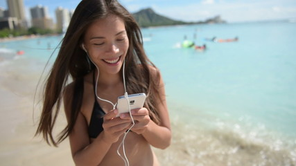 Music on earphones from smartphone - beach woman