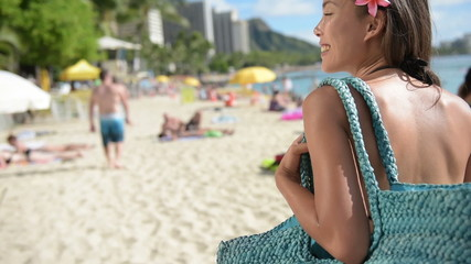 Woman going to the beach in Waikiki with beach bag