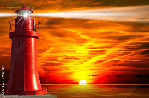 Red Lighthouse with Light Beam at Sunset - 77981390