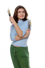 Painter holding her brushes and looking up thoughtfully