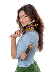 Artist holding her brushes in each hand and smiling