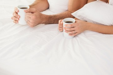 Mid section of young couple having coffee in bed