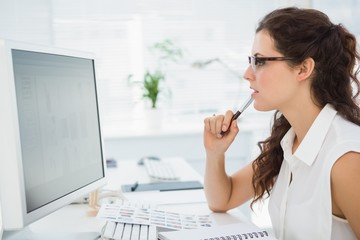 Focused businesswoman with glasses using computer