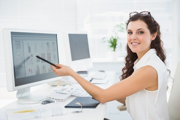 Smiling businessman pointing her computer