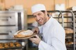 Leinwanddruck Bild - Smiling baker smelling fresh bread