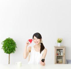 スマートフォンとハートを持って笑う女性
