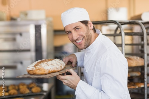 Papiers peints Table preparee Smiling baker smelling fresh bread