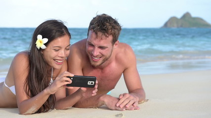 Beach holiday couple using smartphone fun laughing