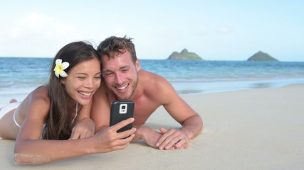 Smart phone - beach holiday couple taking selfie