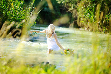 girl in a white sundress on the river starts a wreath of flowers