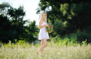 girl in a white sundress and with a wreath of flowers in hand on