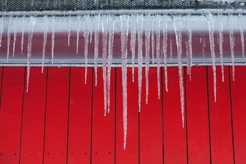 Icicles on the roof. Red wooden background.