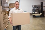 Smiling worker carrying a box