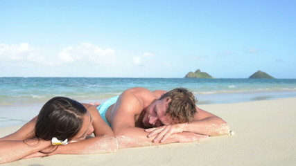 Beach vacations suntan couple relaxing in Hawaii