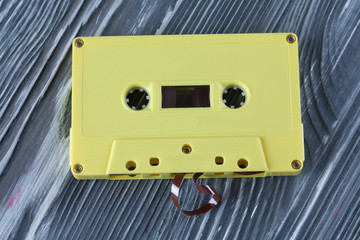 Yellow audio cassette on the gray wooden background.