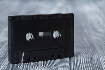Black audio cassette on the gray wooden background.