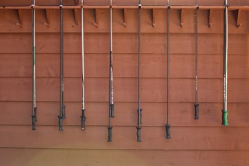 ski poles hanged against wooden wall