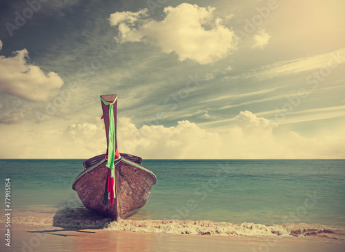 Retro filtered picture of a wooden boat on beach. - 77985154