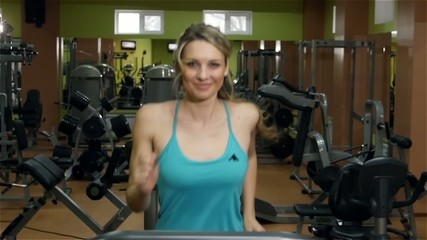 Smiling girl running on fitness track in the gym, slow motion