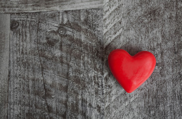 Red heart on a grey wooden background