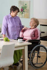 Caregiver helping disabled woman