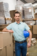 Smiling warehouse worker leaning against boxes
