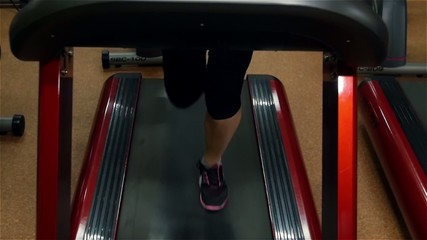Running girl on fitness track in the gym, slow motion