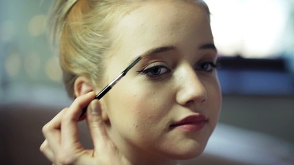 Cosmetician brushing young woman's eyebrows at beauty salon