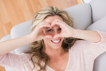 Smiling blonde making heart with her hands