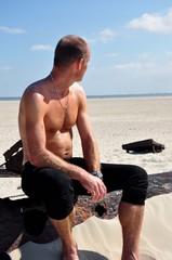 Ein Mann mit freien Oberkörper sitzt am Strand