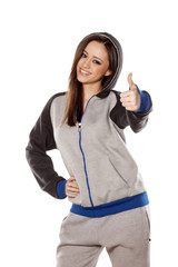 happy young woman in track suits showing thumb up