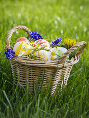 Easter wicker basket full of flowers and easter eggs