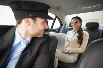 Young businesswoman being chauffeured while working