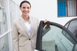 Smiling businesswoman standing beside her car - 77989350
